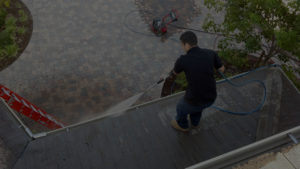 man cleaning outside home