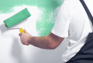 Close-up of worker with roller painting white wall on green